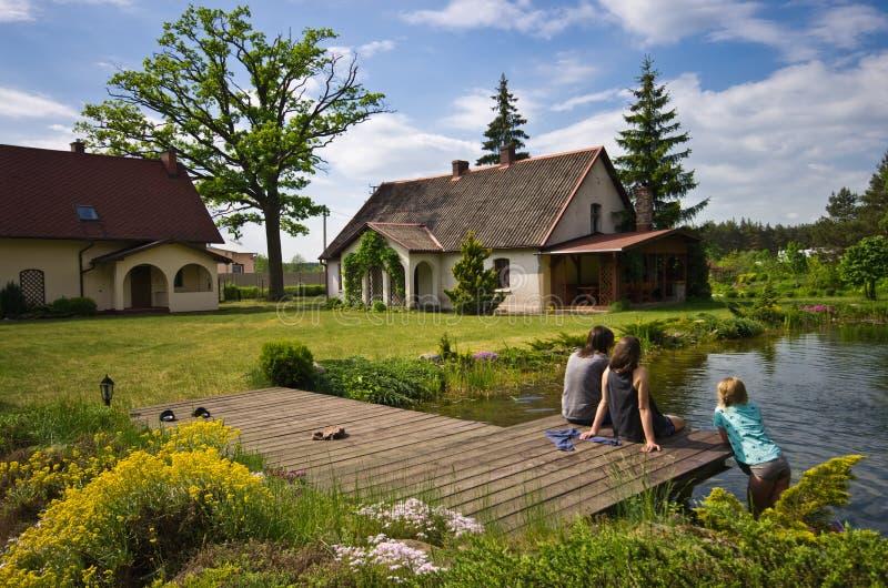 Kobiety i dziewczyny obsiadanie wioska domu basenem obraz royalty free