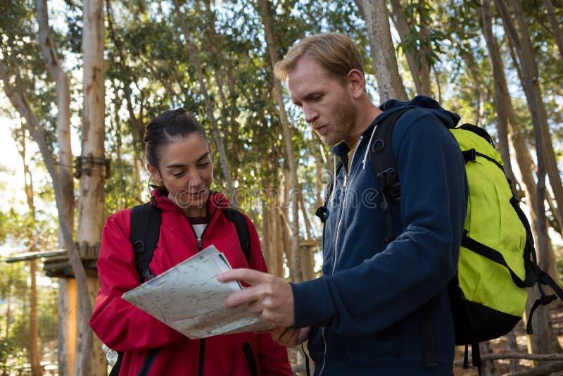 Kobiety i mężczyzna wycieczkowicz z plecaka czytania mapą zdjęcie royalty free