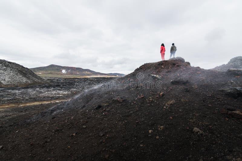 Kobiety i mężczyzny postacie stoi w Krafla wulkanu lawowym polu wokoło Leirhnjukur halnego szczytu, Iceland zdjęcia stock