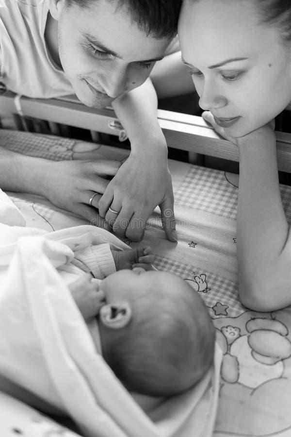Kobiety i mężczyzny spojrzenie przy nowonarodzonym Chłopiec śpi w jego ściąga dziecka tata mama Portret młoda rodzina Szczęśliwy  obraz stock