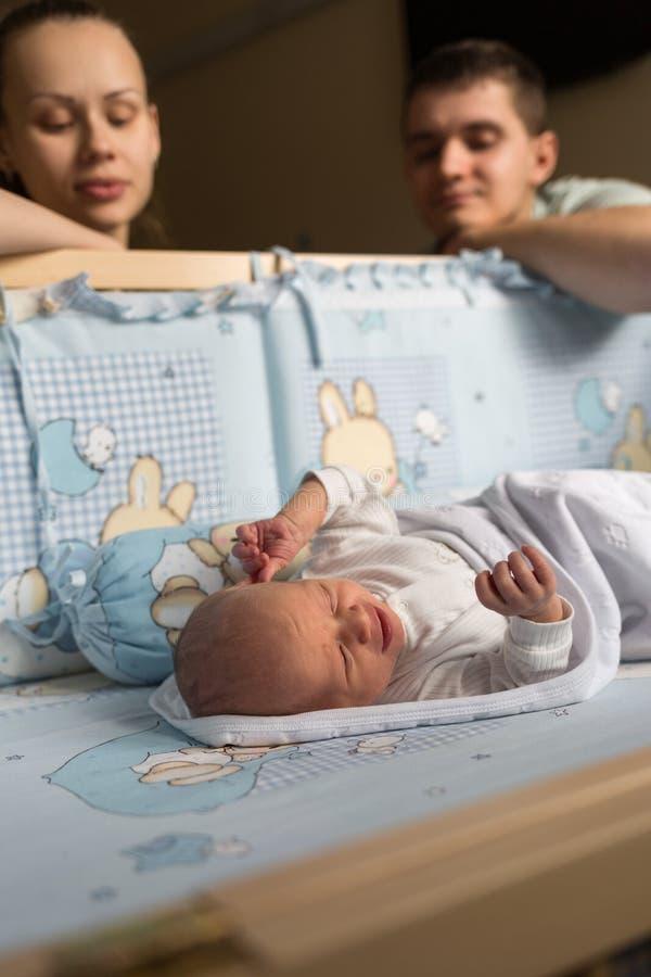 Kobiety i mężczyzny spojrzenie przy nowonarodzonym Chłopiec śpi w jego ściąga dziecka tata mama Portret młoda rodzina Szczęśliwy  obrazy royalty free