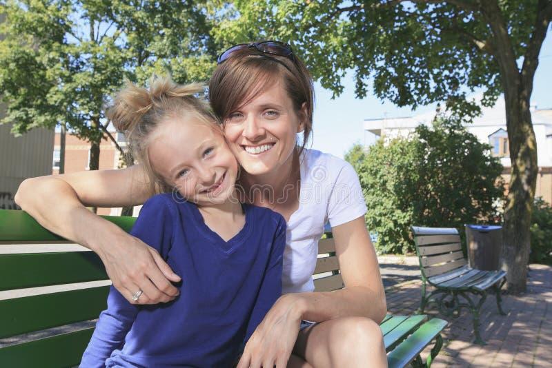 Kobiety i mała dziewczynka siedzą na ławce fotografia stock