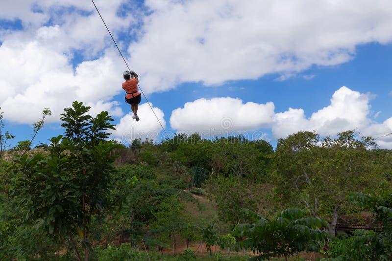 Kobiety jazda w zamek błyskawiczny linii w dolinie Cukrowi młyny w Trinidad Kuba fotografia stock
