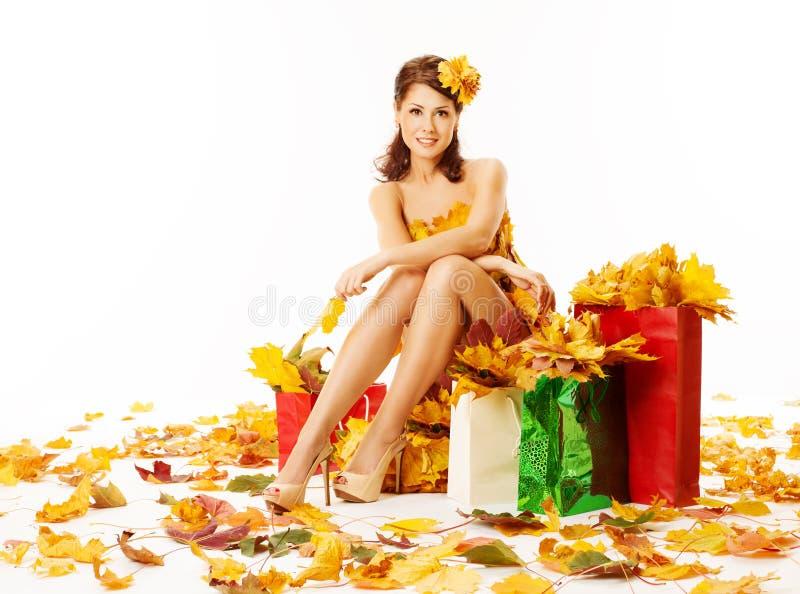Kobiety jesieni zakupy w sukni liście klonowi nad bielem zdjęcia stock