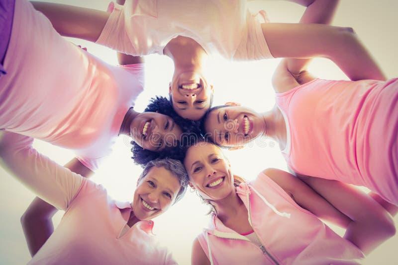 Kobiety jest ubranym menchie dla nowotworu piersi z rękami wokoło obraz stock