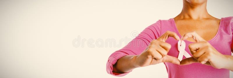 Kobiety jest ubranym różową koszula robi sercu z ich palcami wokoło różowego faborku zdjęcia royalty free