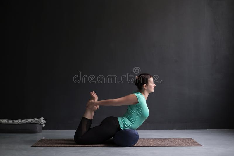 Kobiety joga łęku ćwiczy poza, Dhanurasana używać podgłówek zdjęcia stock