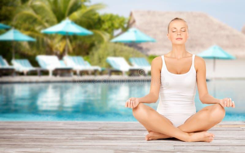 Kobiety joga lotosu ćwiczy poza nad plażowym basenem obraz royalty free