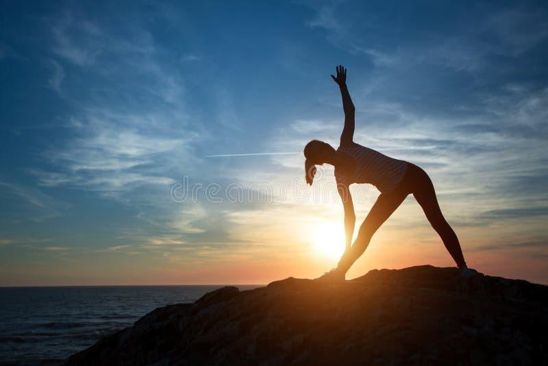 Kobiety joga sylwetka, wykonuje koncentracyjnych ćwiczenia podczas zmierzchu obraz stock