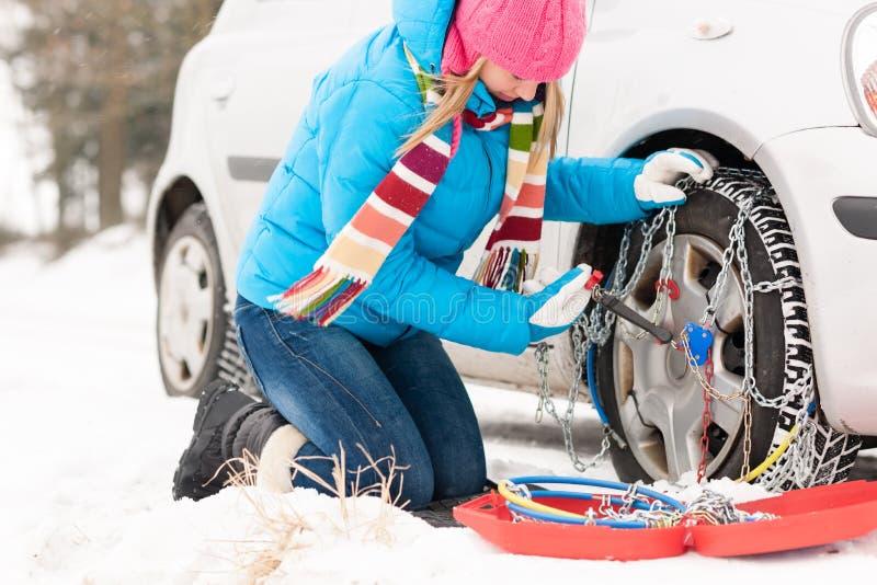 Kobiety kładzenia łańcuchy na samochodowych zima oponach zdjęcia royalty free