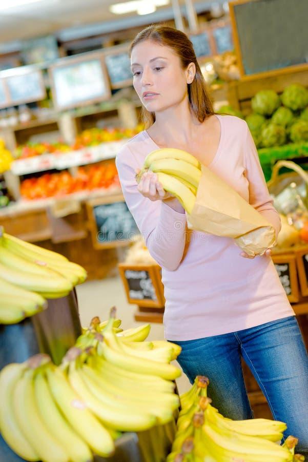 Kobiety kładzenia banan wśrodku paperbag zdjęcie stock