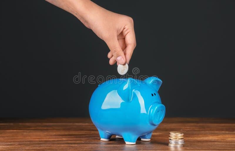Kobiety kładzenia moneta w prosiątko banka obrazy stock