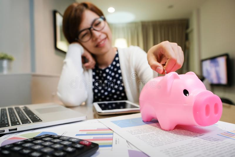Kobiety kładzenia moneta W Różowym prosiątko banku zdjęcie stock