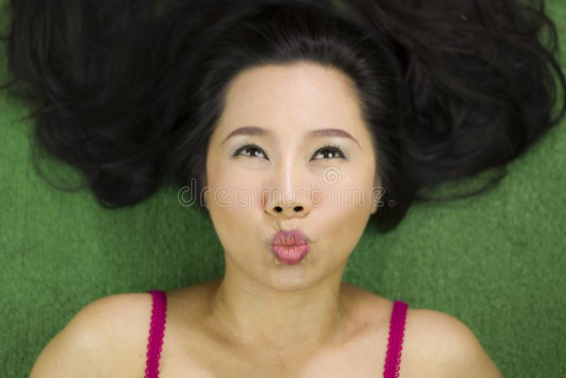 Kobiety k?ama na zielonej trawie, ?miesznym u?miechu, pi?knego i dzia?ania, Tajlandzka kobieta k?a?? w d?? na zielonej trawie zdjęcia royalty free