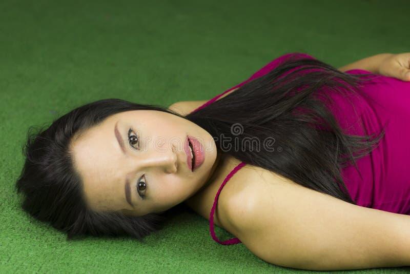 Kobiety k?ama na zielonej trawie, Tajlandzkiej kobiecie k?a?? w d?? na zielonej trawie, pi?knej i marzycielskiej, relaksuje podcz obrazy stock