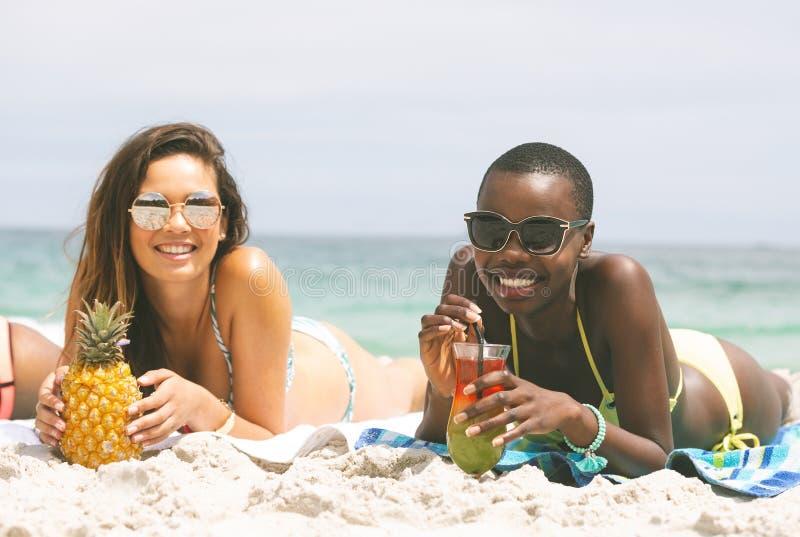 Kobiety kłama przy plażą podczas gdy mieć ananasa zdjęcie stock