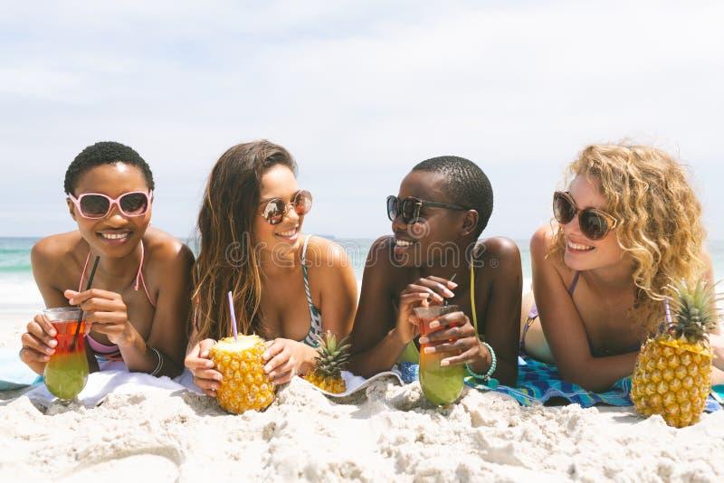 Kobiety kłama przy plażą podczas gdy mieć ananasowego sok obrazy stock