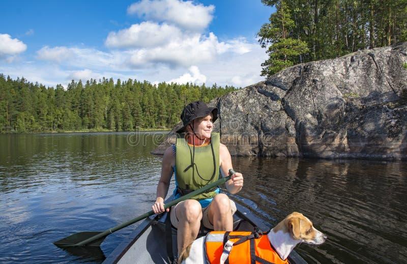 Kobiety kajakarstwo na jeziorze z psem zdjęcie royalty free