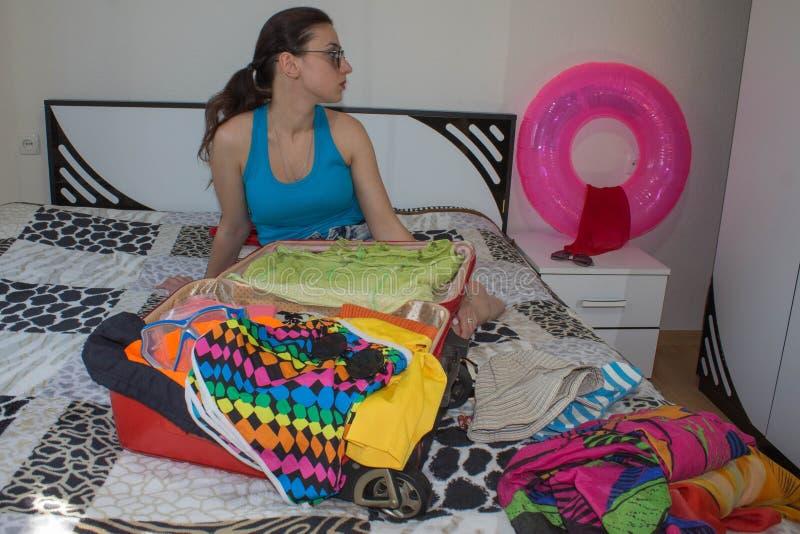 Kobiety kocowania narządzanie dla wakacje Młodej Dziewczyny kocowania walizka na łóżku w domu obrazy stock