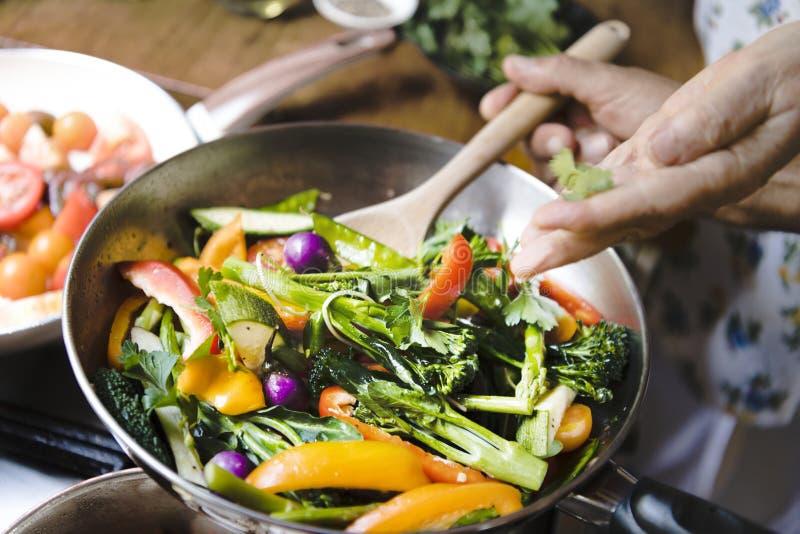 Kobiety kucharstwa fertania smażący warzywa zdjęcie royalty free