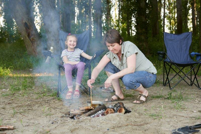 Kobiety kulinarny jedzenie, ludzie obozuje w lesie, rodzinny aktywny w naturze, rozognia ogienia, lato sezon obraz stock