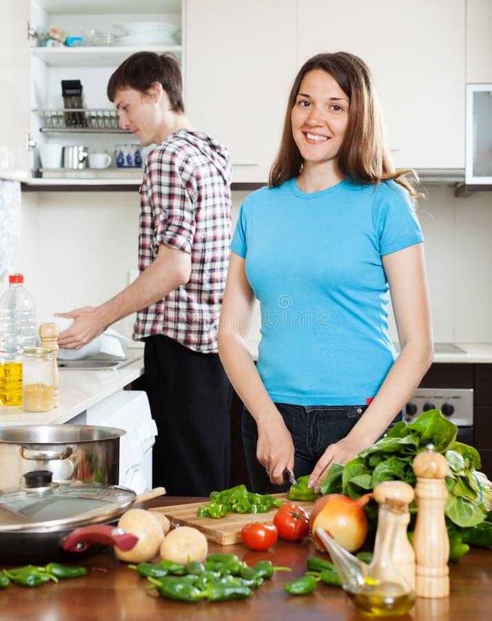Kobiety kulinarny jedzenie podczas gdy mężczyzna domycia naczynia fotografia stock