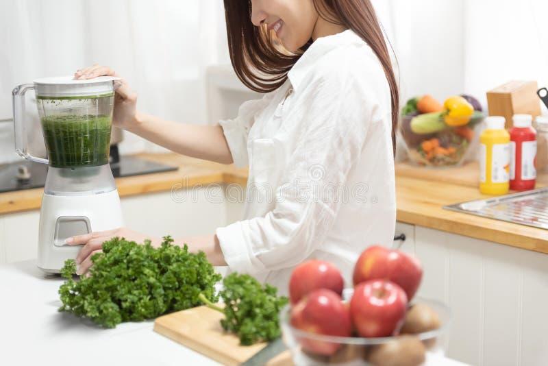 Kobiety kulinarny smoothie z świeżymi owoc i brokułami z blender fotografia royalty free