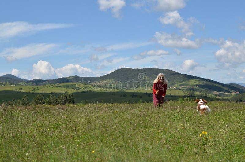 Kobiety kursowanie z Jej psem w krajobrazie zdjęcie stock