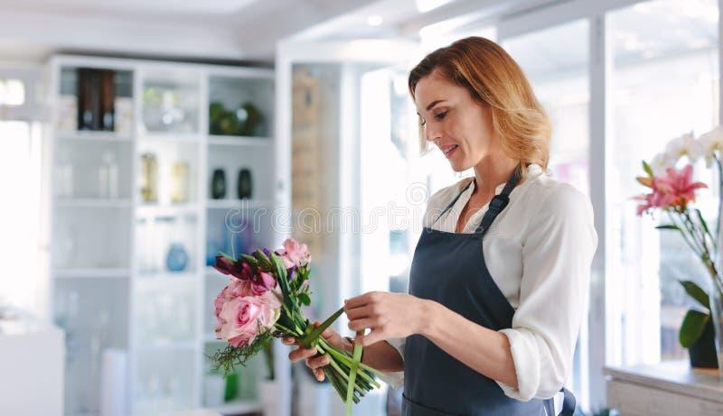 Kobiety kwiaciarnia przygotowywa bukiet przy jej sklepem obraz stock