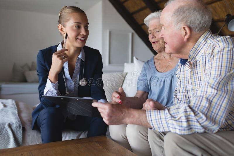 Kobiety lekarka i starsza para dyskutuje nad schowkiem zdjęcia stock