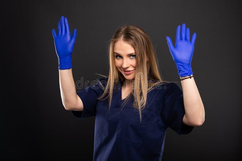 Kobiety lekarka jest ubranym pętaczki i rękawiczki pokazuje ręki fotografia royalty free