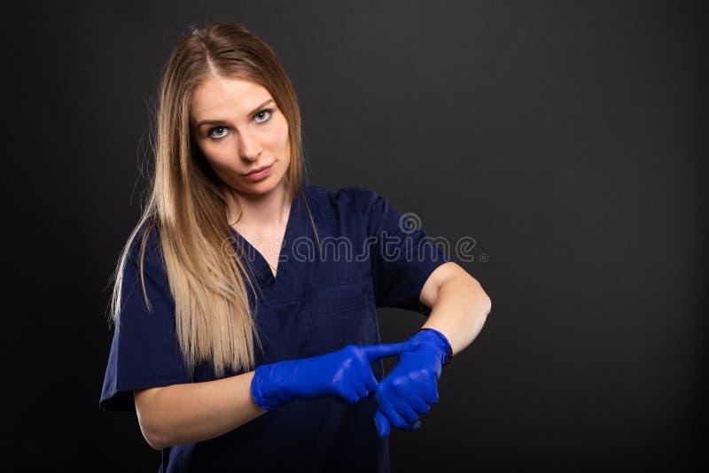 Kobiety lekarka jest ubranym pętaczki i rękawiczki robi opóźnionemu gestowi obraz royalty free