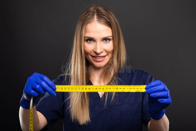 Kobiety lekarka jest ubranym pętaczki pokazuje pomiarowej taśmy zdjęcia royalty free
