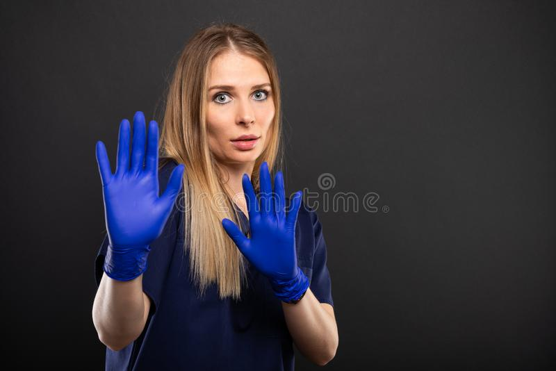 Kobiety lekarka jest ubranym pętaczki robi okaleczającemu gestowi obraz stock
