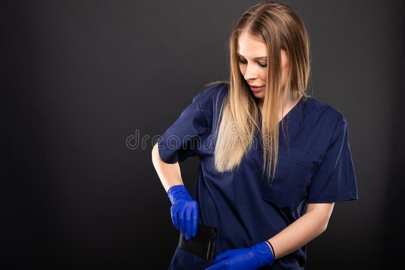 Kobiety lekarka jest ubranym pętaczki stawia out portfel zdjęcie stock