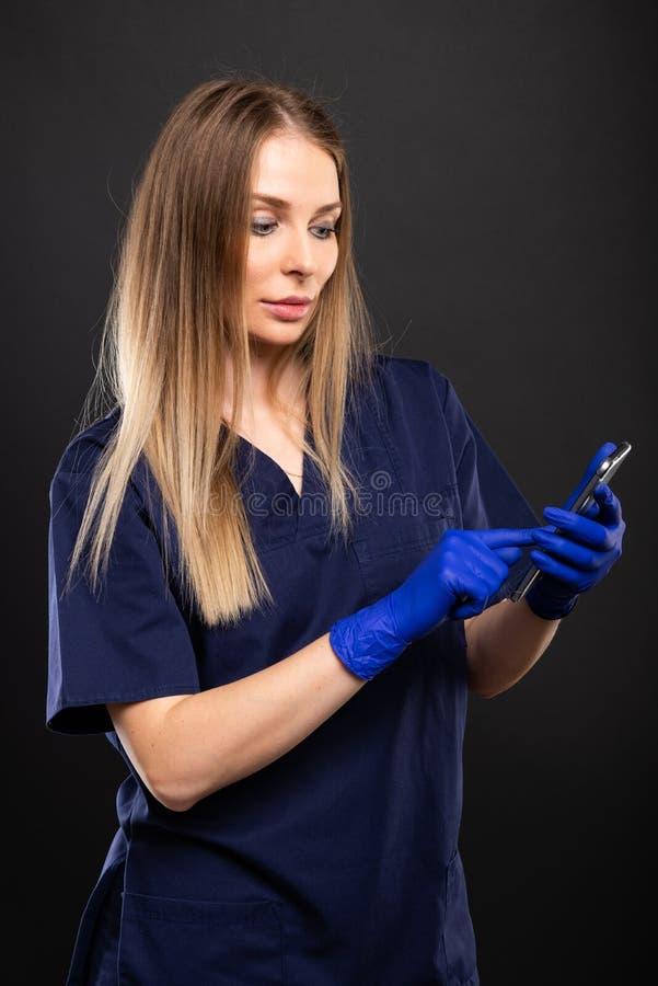 Kobiety lekarka jest ubranym pętaczki używać smartphone fotografia royalty free
