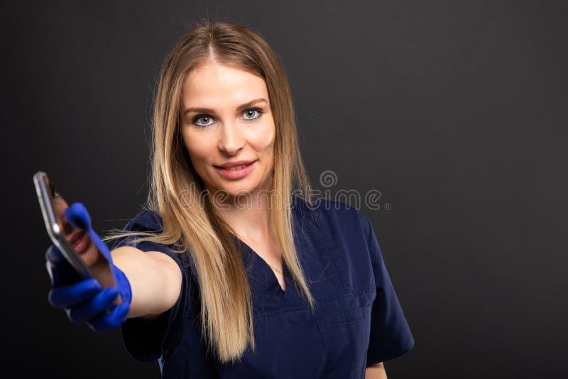 Kobiety lekarka jest ubranym pętaczki wręcza smartphone obrazy royalty free