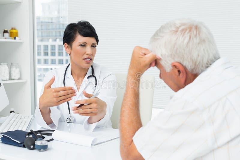 Kobiety lekarka wyjaśnia raporty starszy pacjent obraz royalty free