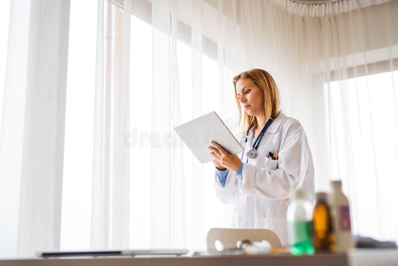 Kobiety lekarka z pastylką pracuje przy biurem zdjęcie stock