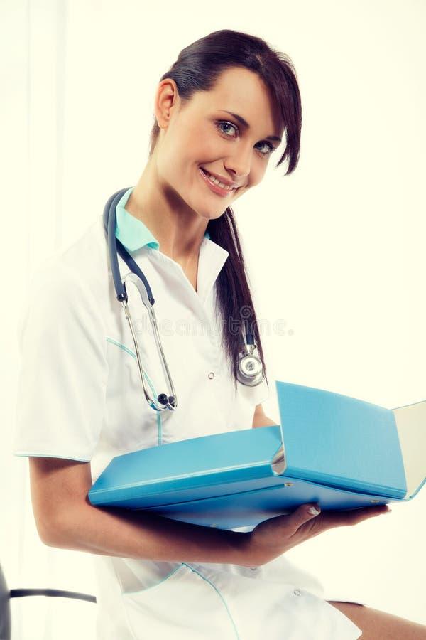 Kobiety lekarka z stetoskop pozycją przy biurowym i ono uśmiecha się przy kamerą zdjęcie stock