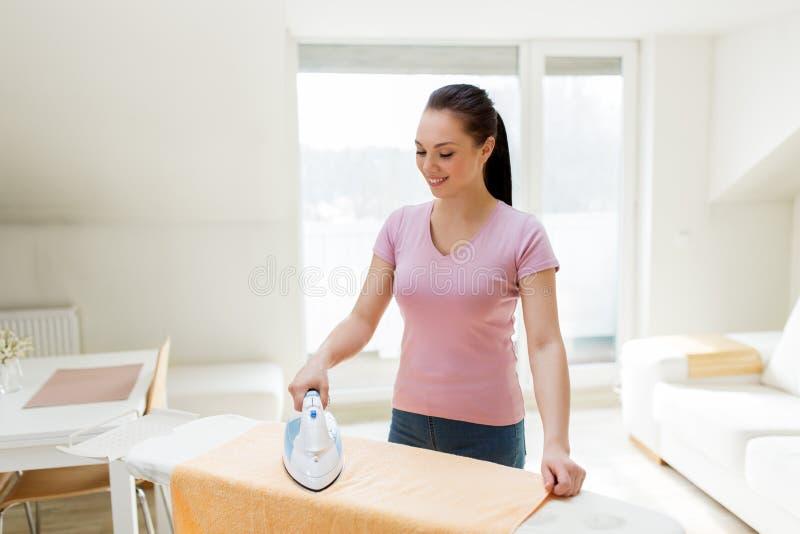 Kobiety lub gospodyni domowej prasowania ręcznik żelazem w domu zdjęcia stock
