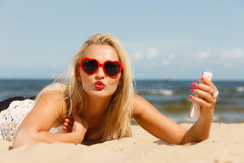 Kobiety lying on the beach na piaskowatej plaży używać telefon komórkowego obrazy royalty free