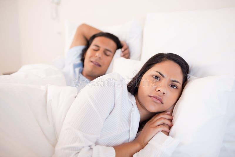 Kobiety lying on the beach obudzony obok jej sypialnego chłopaka fotografia stock
