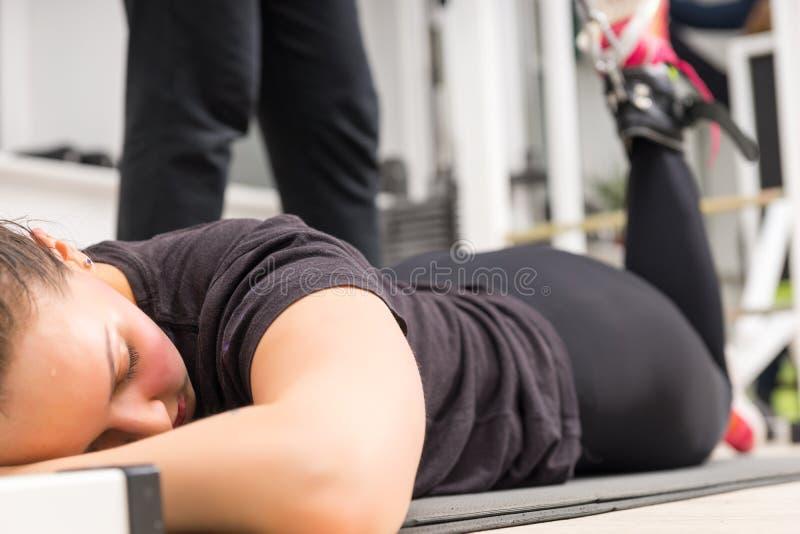 Kobiety lying on the beach w gym używać nogi podwyżki maszynę obraz stock