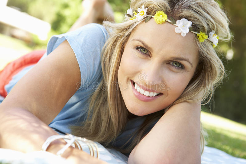 Kobiety lying on the beach W parku Jest ubranym kwiaty Wokoło włosy obraz stock