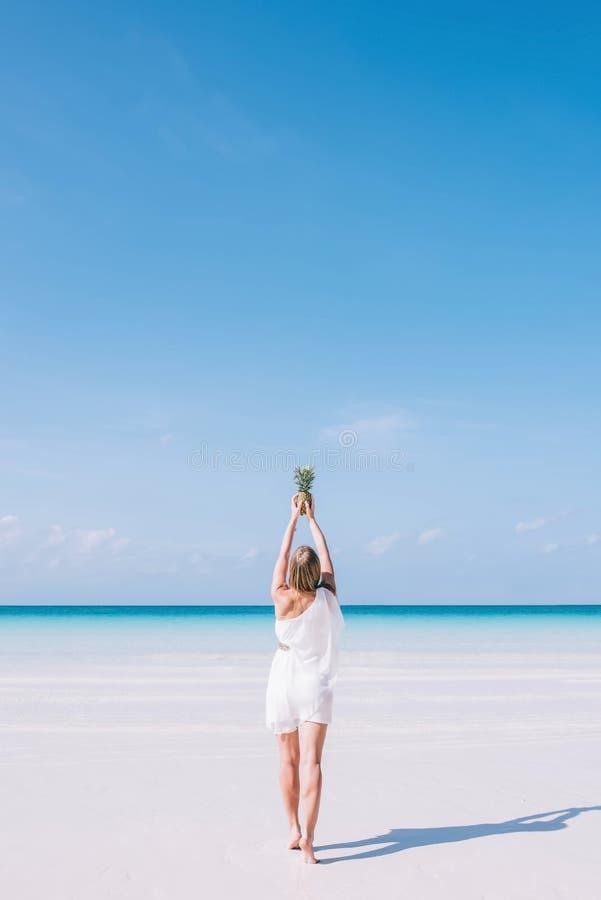 Kobiety młodzi Europejscy długie włosy stojaki na białej piaskowatej plaży oceanem Dziewczyna w białej sukni trzyma ananasa obrazy stock