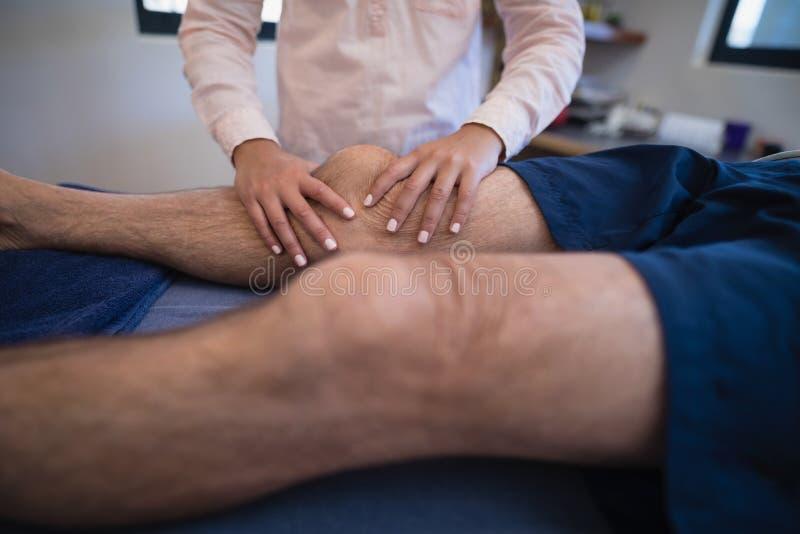 Kobiety masowania doktorski kolano pacjent obraz stock