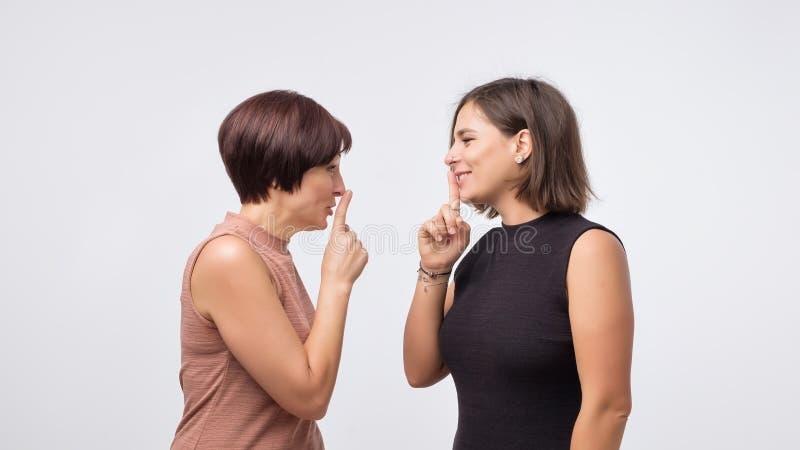 Kobiety matka i córka plotkuje sekret odizolowywającego nad szarym tłem i mówi zdjęcie stock