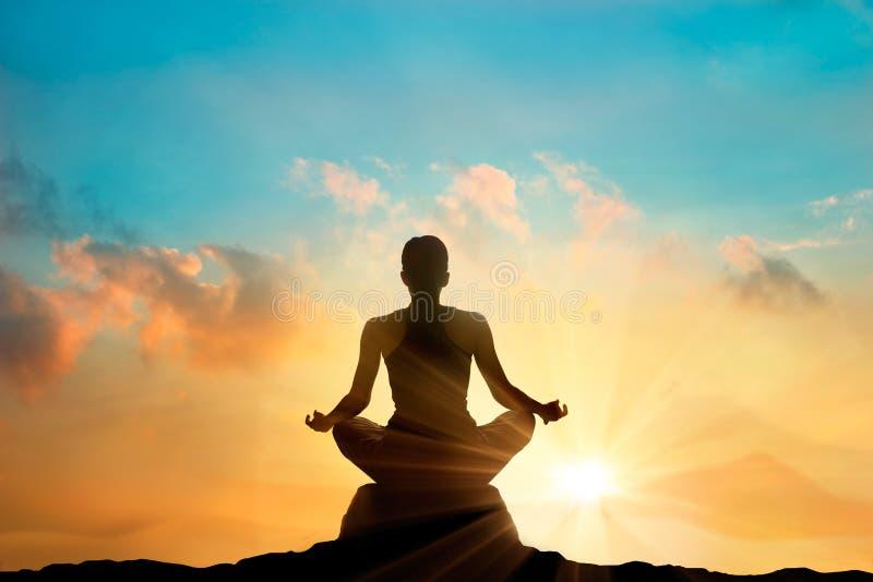 Kobiety medytuje na wysokiej górze w zmierzchu tle obrazy royalty free