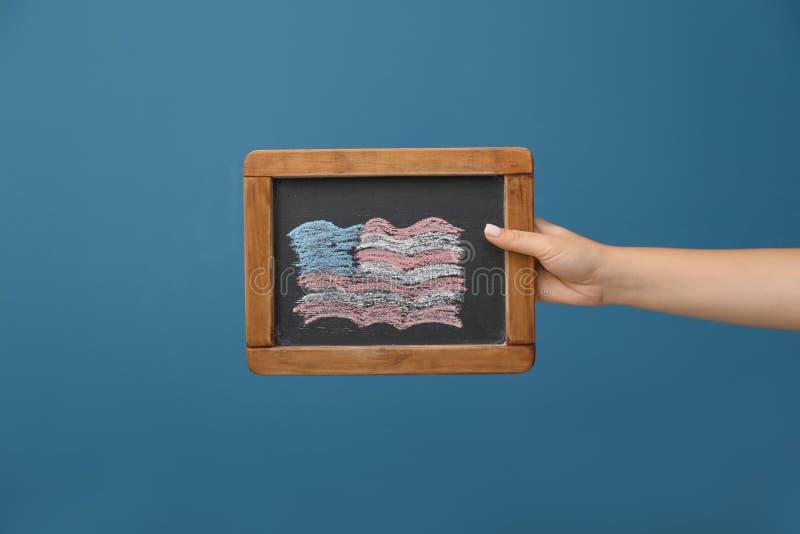 Kobiety mienia chalkboard z rysunkiem Amerykańska flaga państowowa na koloru tle zdjęcie royalty free